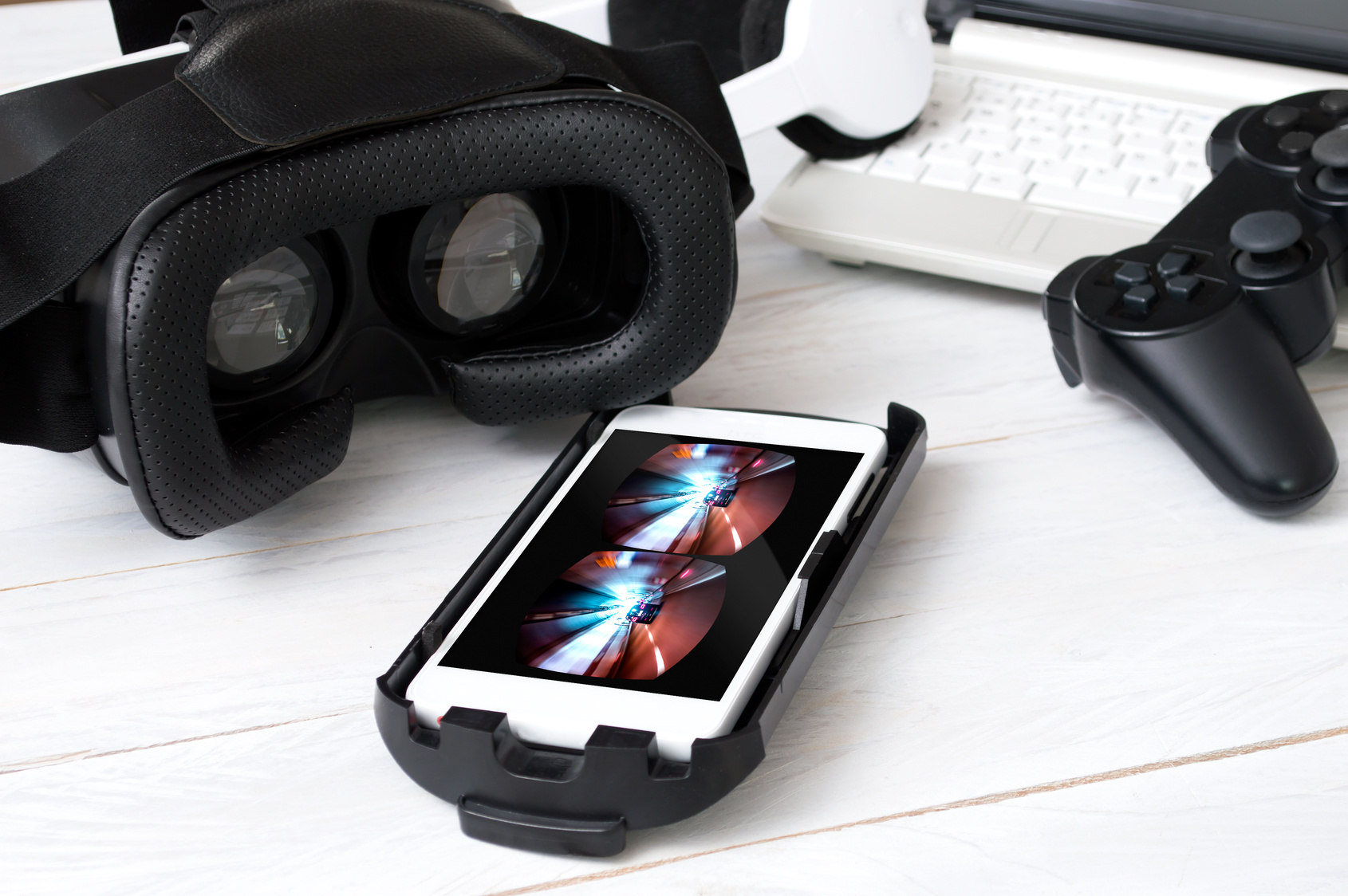 Smartphone laying on desk and prepared to play with VR googles. Game on screen was created in graphic program